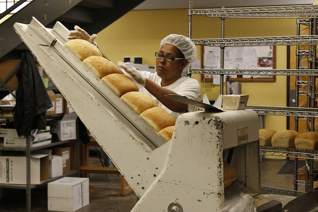 An Annie's employee slices bread.
